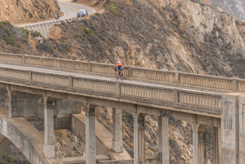 Ciclista sobre el puente de la cala de Bixby en la puesta del sol en Big Sur, California, los E.E.U.U. fotografía de archivo
