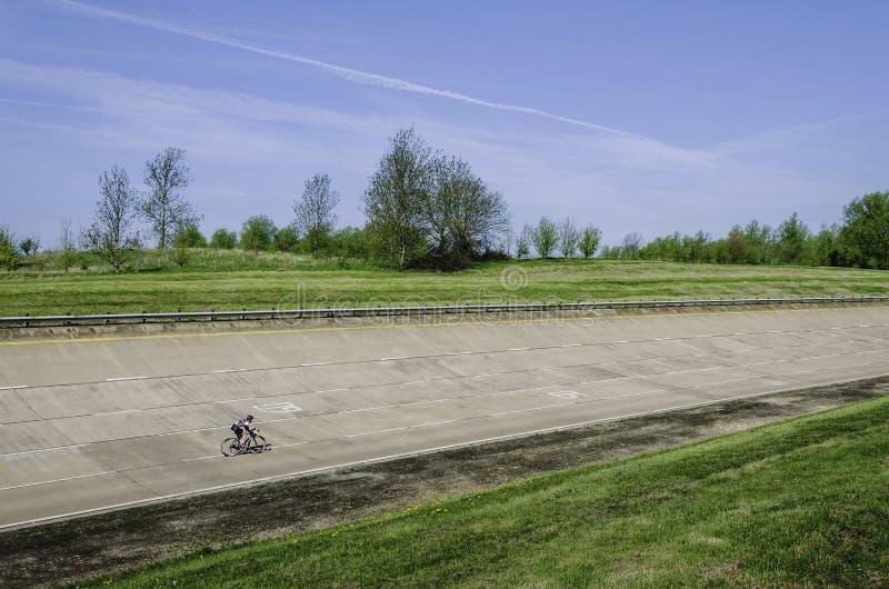 Ciclista solo sulla pista vuota fotografia stock