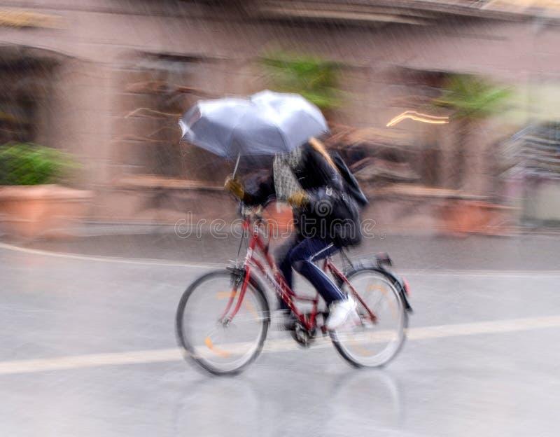 Ciclista sulla carreggiata della citt? nel mosso nel giorno piovoso fotografie stock libere da diritti