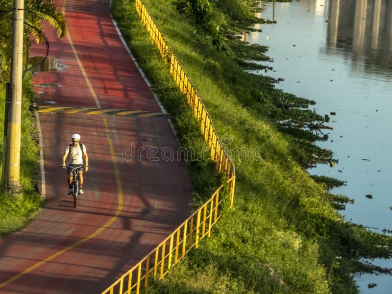 Ciclista sulla pista ciclabile vicino del fiume di Pinheiros, costa Ovest di Sao Paulo immagine stock libera da diritti