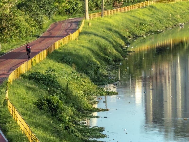 Ciclista sulla pista ciclabile vicino del fiume di Pinheiros, costa Ovest di Sao Paulo immagini stock libere da diritti