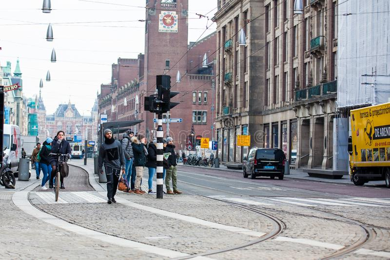 Ciclista in un giorno di molla in anticipo di freddo al vecchio distretto centrale di Amsterdam fotografia stock libera da diritti