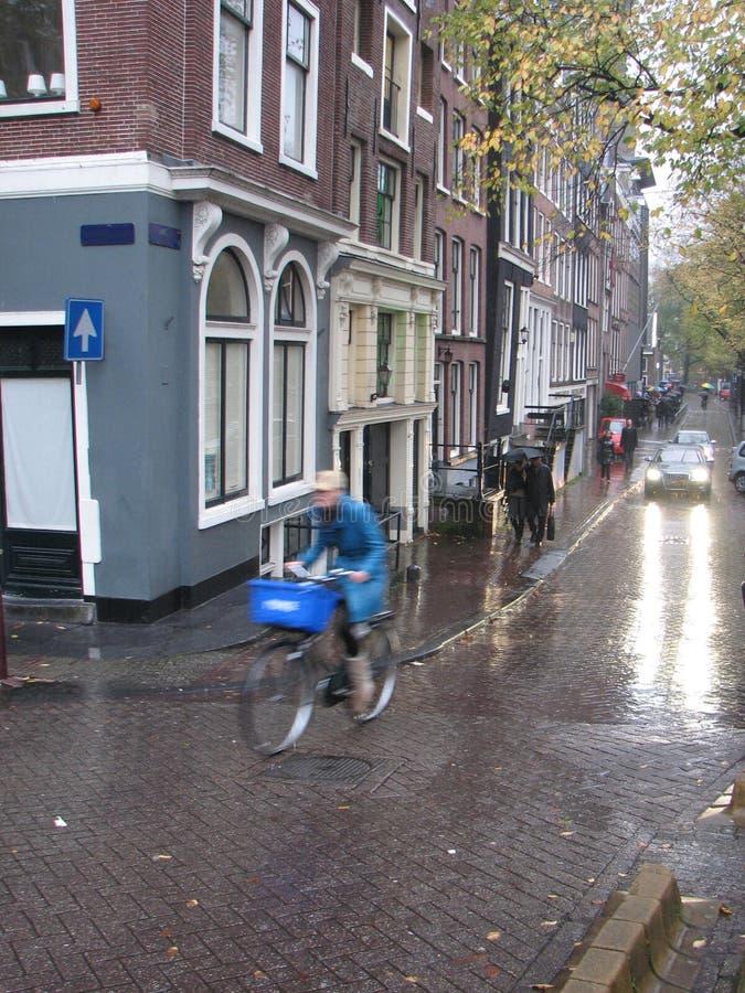 Ciclista in via piovosa a Amsterdam immagini stock libere da diritti