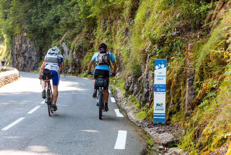 Ciclistas aficionados que suben el d'Aubisque de la columna fotos de archivo libres de regalías