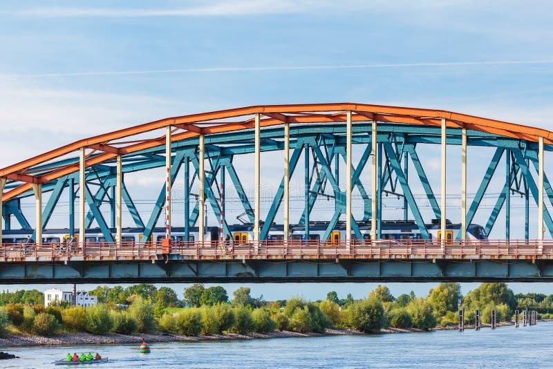 Ciclistas e trem que cruzam a ponte de IJssel em Zutphen imagem de stock