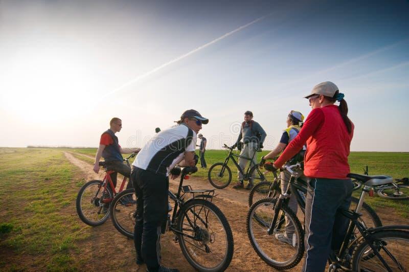 Ciclistas en la puesta del sol fotos de archivo
