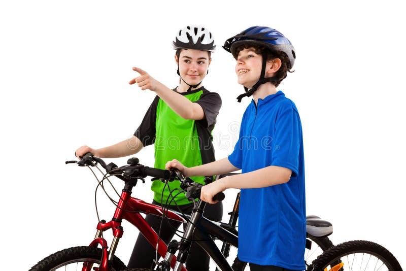 Ciclistas - menino e menina isolados no branco imagem de stock