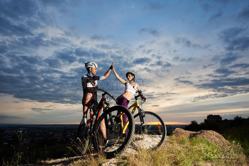 Ciclistas positivos que sorriem e que highing cinco em bicicletas imagem de stock royalty free