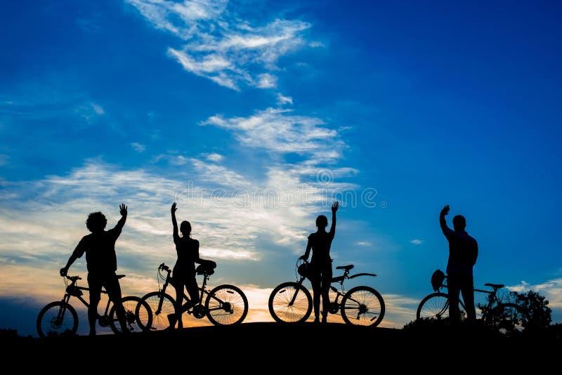 Ciclistas que agitan con las manos en la igualación del cielo de la puesta del sol imágenes de archivo libres de regalías