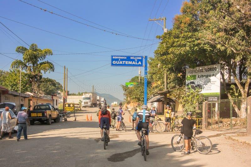 Ciclistas que cruzam a beira das Honduras à Guatemala imagem de stock