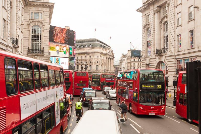 Ciclistas que luchan el espacio con los coches y los autobuses en las calles de Londres, Reino Unido imagen de archivo