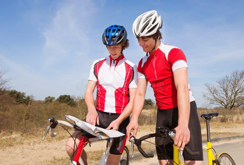 Ciclistas que olham um mapa imagem de stock royalty free