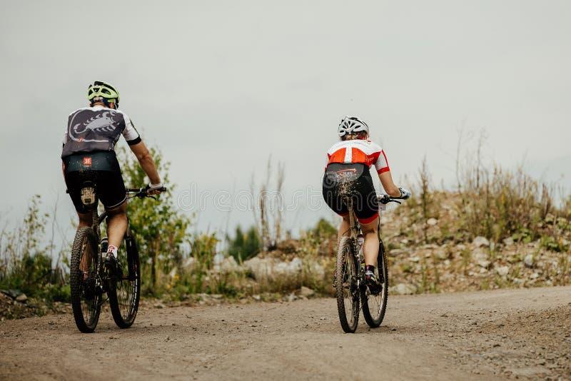 ciclistas traseiros homem e mulher que montam junto na fuga foto de stock