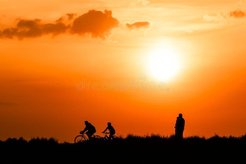 Ciclistas y caminante en la puesta del sol imagen de archivo