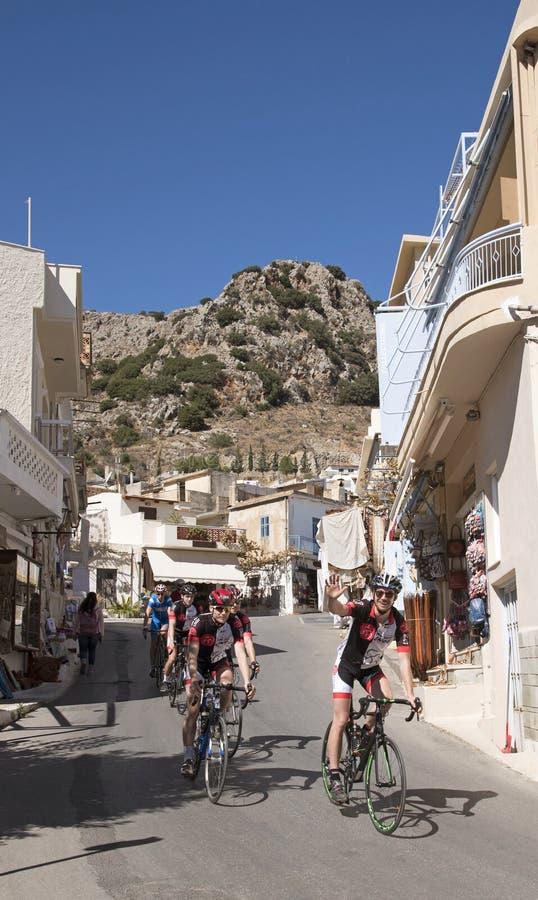 Ciclisti che visitano Creta che passa attraverso il villaggio di Kritsa fotografia stock