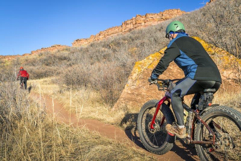 Ciclisti in mountain-bike che guidano traccia alle colline pedemontana di Colorado fotografia stock