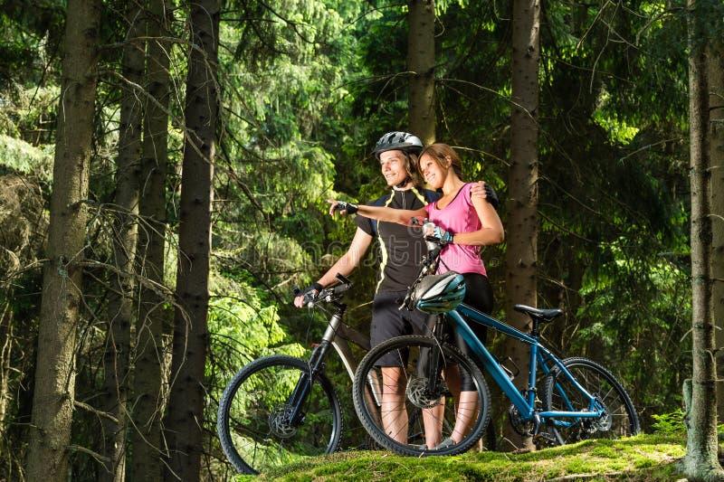 Ciclisti teenager sorridenti che stanno ed indicare fotografia stock