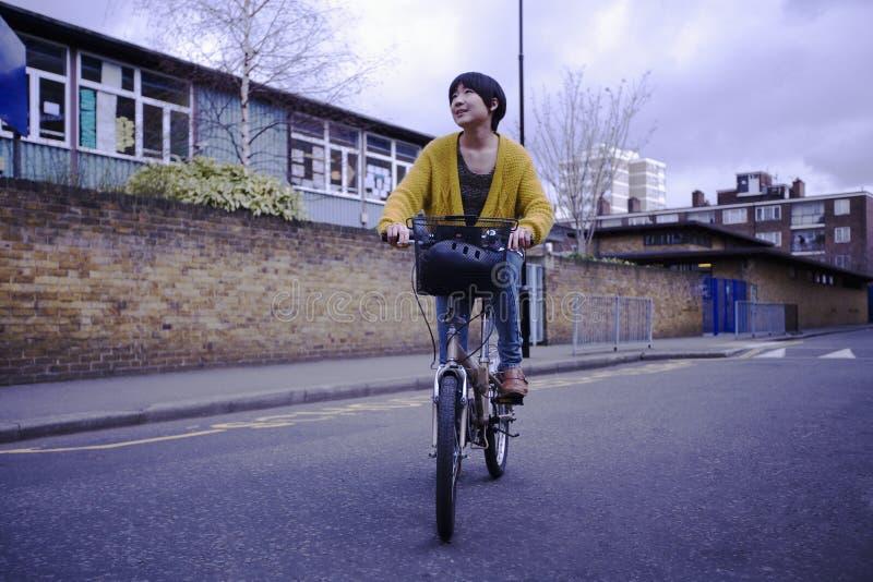 Ciclo da equitação da mulher na rua fotografia de stock