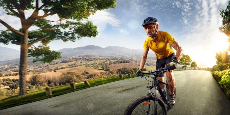 Ciclo del cavaliere della bicicletta nel paesaggio della natura delle colline del villaggio strada nel moto che bluring fotografia stock