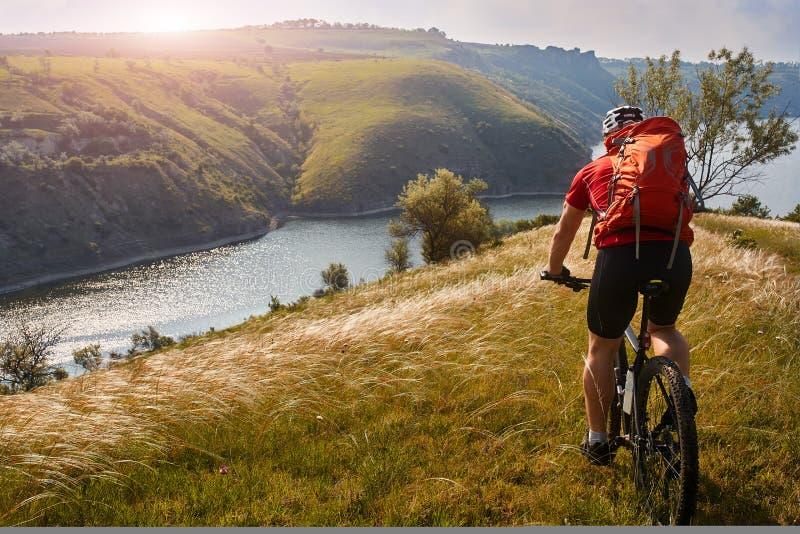 Ciclo joven de la montaña del montar a caballo del cylcist del atleta en la colina sobre el río en el campo foto de archivo