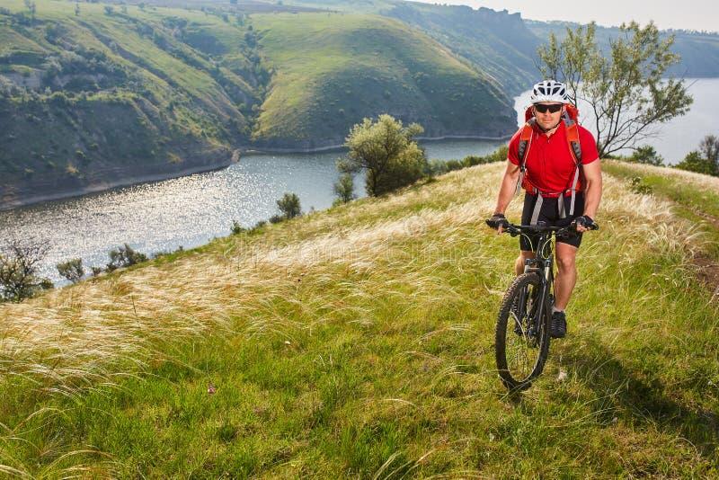 Ciclo joven de la montaña del montar a caballo del cylcist del atleta en la colina sobre el río en el campo fotografía de archivo libre de regalías