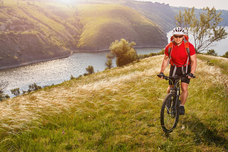 Ciclo joven de la montaña del montar a caballo del cylcist del atleta en la colina sobre el río en el campo fotografía de archivo