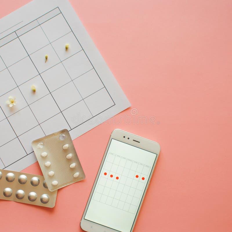 Ciclo menstrual Calendario para el mes con las marcas y una aplicación móvil en la pantalla del smartphone imágenes de archivo libres de regalías