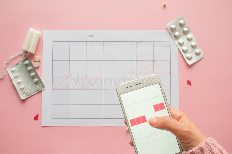 Ciclo menstrual Calendario para el mes con las marcas y una aplicaci?n m?vil en la pantalla del smartphone foto de archivo libre de regalías