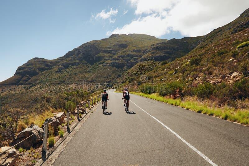Ciclo practicante de Triathletes en la carretera nacional abierta imagen de archivo libre de regalías