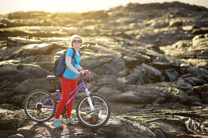 Ciclo turístico joven en campo de lava en Hawaii Caminante femenino que dirige al área de visión de la lava en Kalapana en su bic fotos de archivo libres de regalías