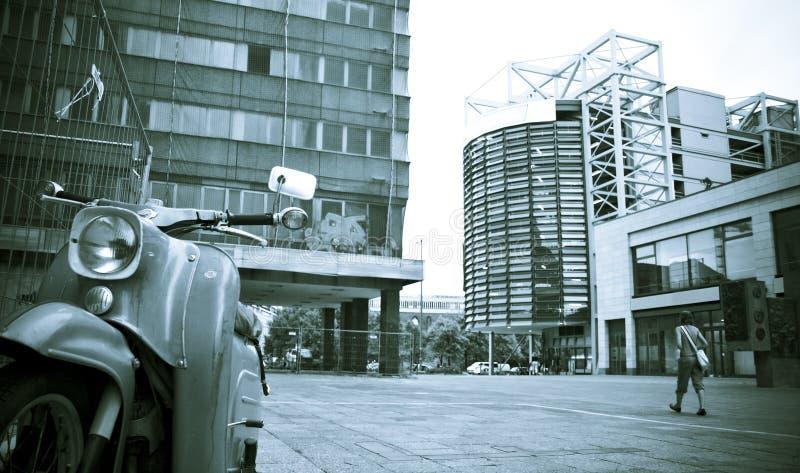 Ciclomotor en cara de la plaza urbana foto de archivo