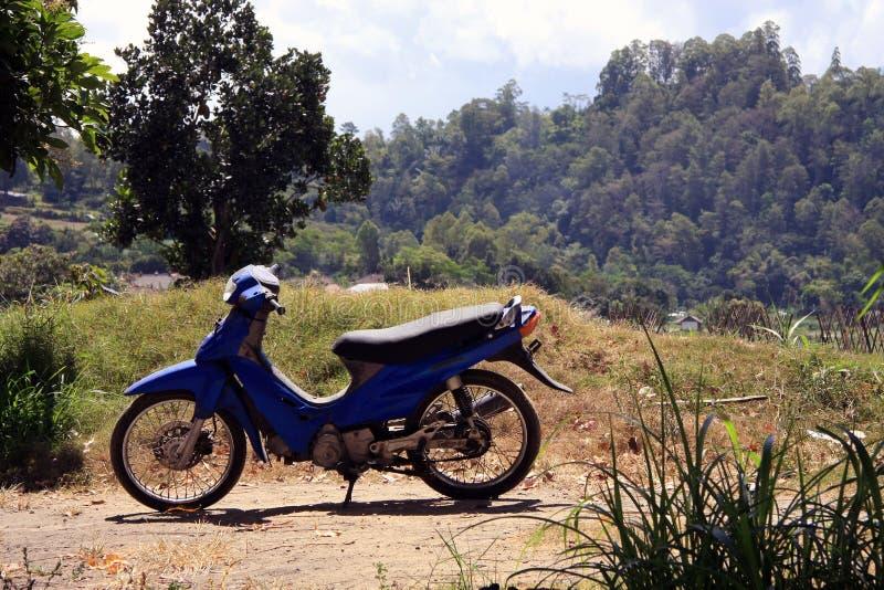 Ciclomotor/moto azules viejos en Bali rural imagen de archivo libre de regalías