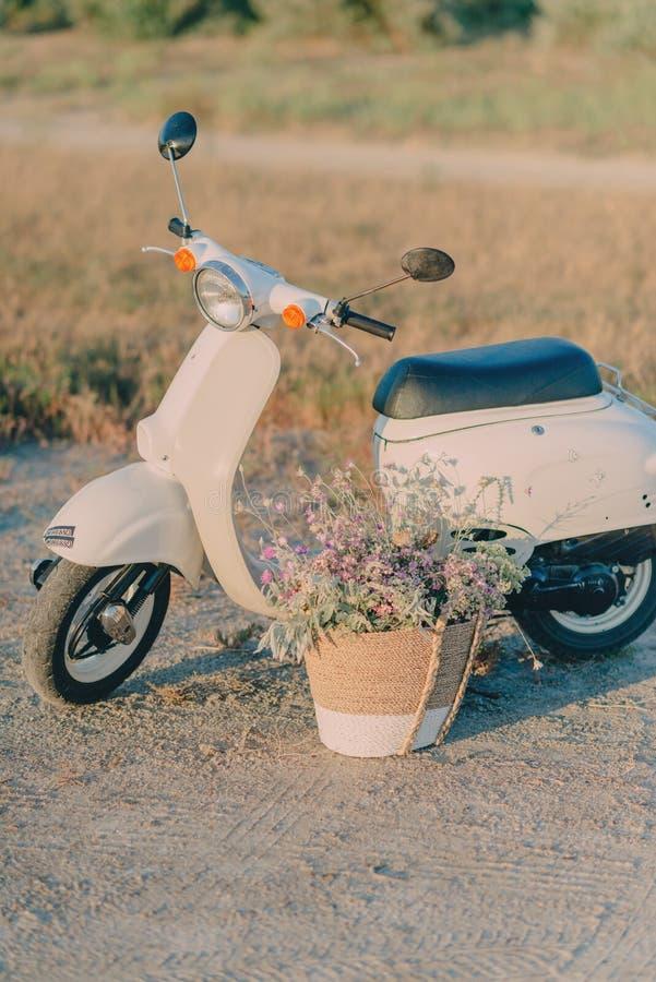 Ciclomotore di bianco e un canestro dei fiori immagini stock