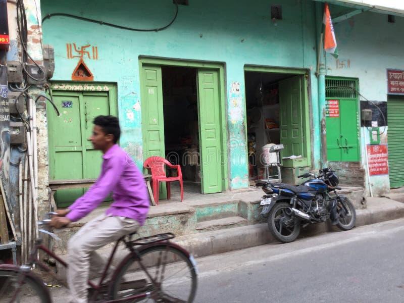 Ciclos del hombre por el edificio verde en la camisa rosada, la India imagen de archivo libre de regalías