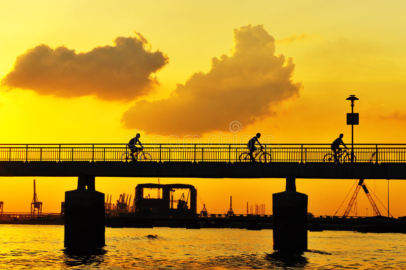 Cicyling on the bridge at sunset royalty free stock photo