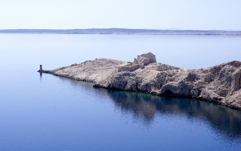Cidade bizantina antiga de Fortica, ruínas na borda da ilha do Pag, Croácia, com uma reflexão do azul de turquesa no mar foto de stock
