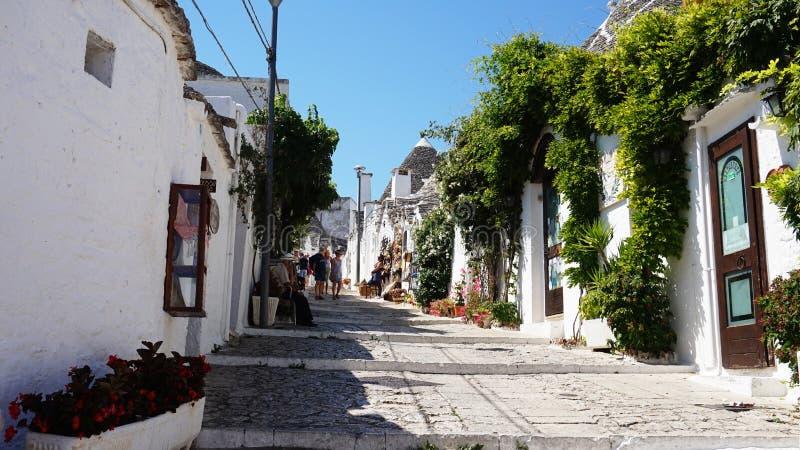 Cidade bonita de Alberobello com as casas do trulli entre plantas verdes e flores, distrito turístico principal, região de Apulia imagens de stock royalty free