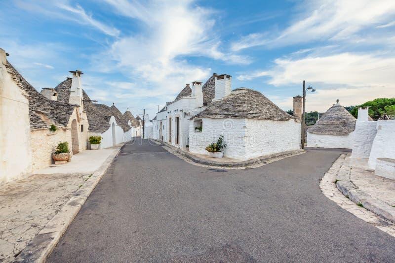 Cidade bonita de Alberobello com as casas de Trulli entre plantas verdes e flores, região de Apulia, Itália do sul foto de stock