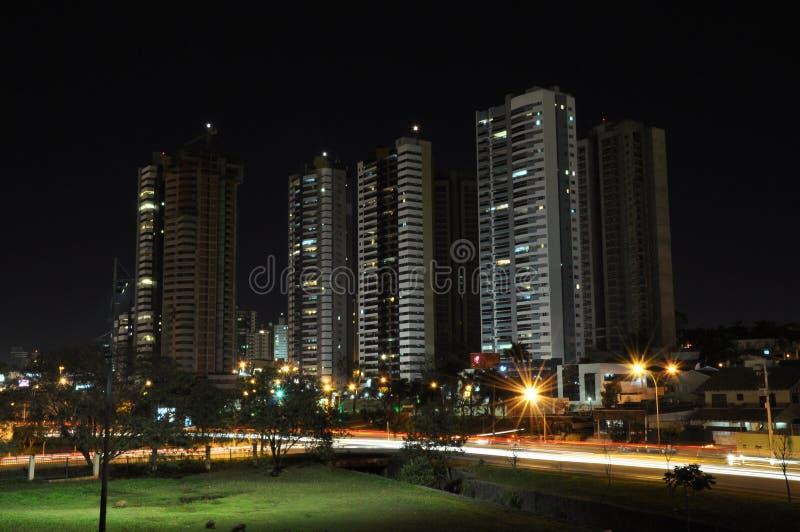 Cidade com poucas construções e muitas luzes dos carros na estrada borrada imagens de stock