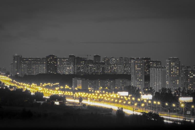 Cidade da noite com um céu escuro A rua com lanternas amarelas gosta de sóis pequenos fotografia de stock