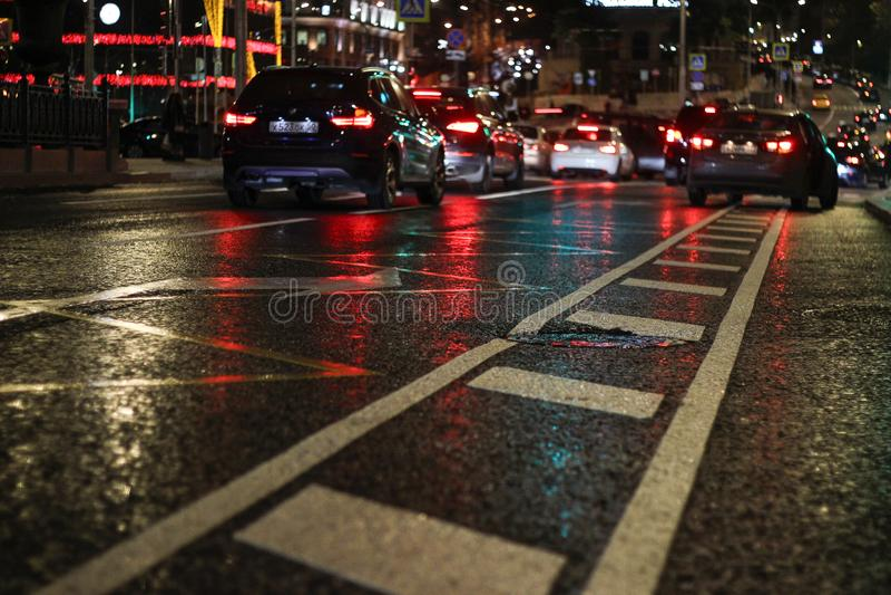 Cidade da noite O asfalto no foco é visível seu equipamento técnico Asfalto após a chuva molhada imagem de stock royalty free