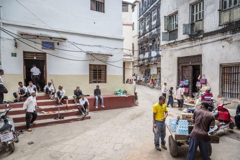 CIDADE DA PEDRA, ZANZIBAR - 15 DE AGOSTO DE 2015: Populações locais numa rua típica de um beco na Cidade de Stone Stone Town é a  imagens de stock