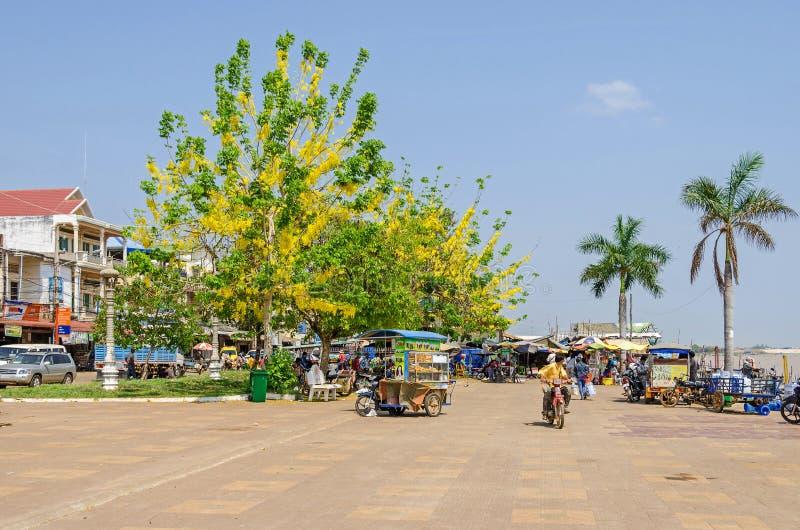 Cidade de Chhnang do Kampong no banco do Mekong River com árvores de florescência, bicicletas motorizadas, carros e um vendedor a imagens de stock