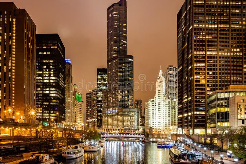 A cidade de Chicago iluminou construções na noite Reflexões no canal do rio fotos de stock royalty free