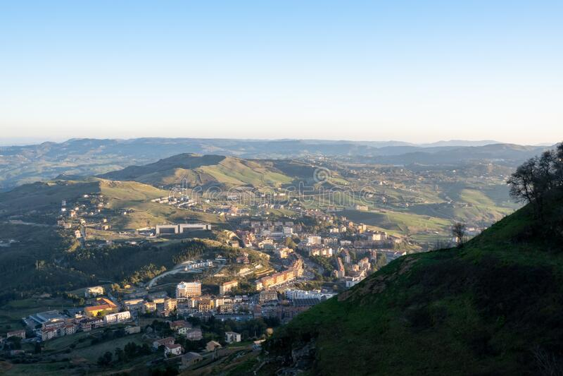 Cidade de Contrada Santa Lúcia sob o Castelo de Enna, Sicília, Itália ao pôr do sol com sombras imagens de stock