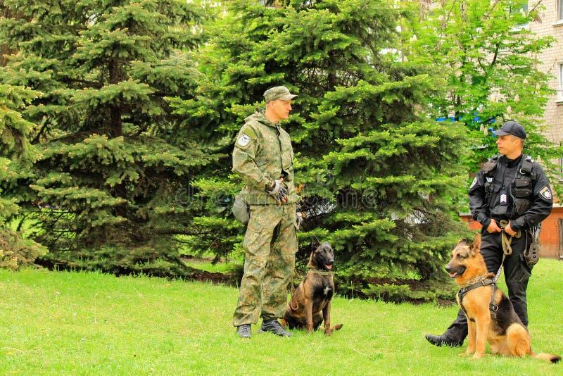 Cidade de Dnipro, Dnepropetrovsk, Ucr?nia, o 9 de maio de 2018 Alimentadores de cão ucranianos da polícia com cães-pastor treinad fotografia de stock