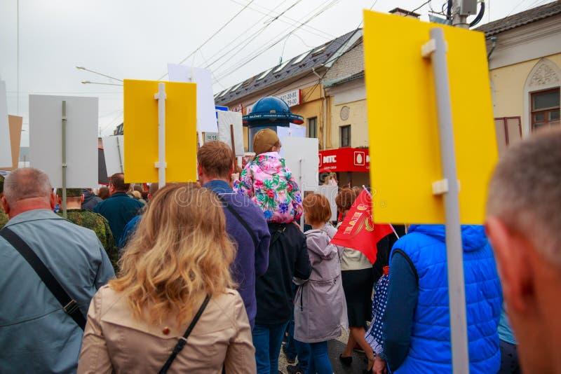 Cidade de Kaluga, Rússia - em maio de 2019: o forragem-tampão vestindo da menina assenta em ombros de seu pai e participa na para fotografia de stock royalty free