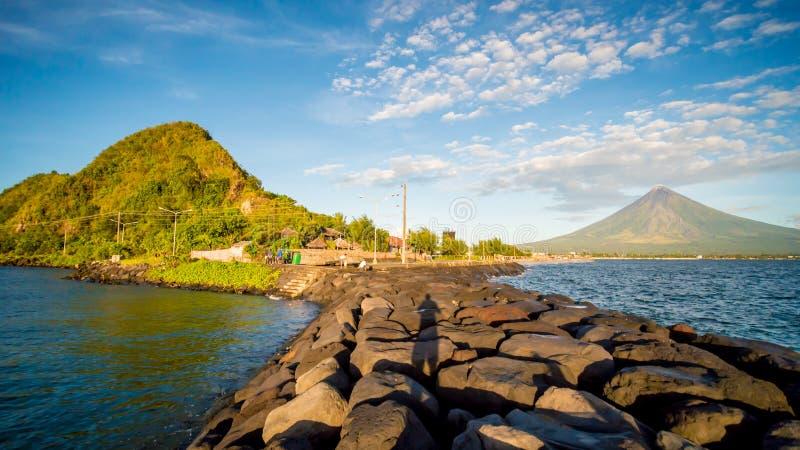 Cidade de Legazpi, Luzon, Filipinas - monte teares do vulcão de Mayon sobre a cidade como o dia a dia vai sobre imagens de stock