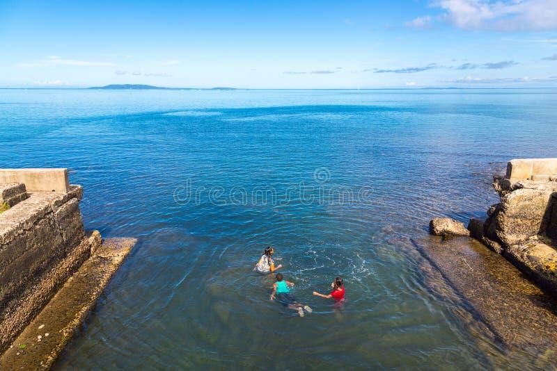 Cidade de Levuka, Fiji As crianças Melanesian fijian nativas estão nadando fora da terraplenagem, ilha de Ovalau, Fiji, Melanesia imagem de stock