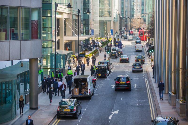 Cidade de Londres, opinião da rua de Canary Wharf com lols de executivos de passeio e de transporte na estrada Negócio e vida mod fotos de stock royalty free